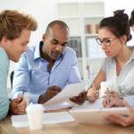 4 pessoas conversando e vendo projetos com papeis e notebook sobre ferramentas de gerenciamento de projetos